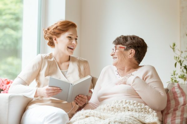 Happy nurse reading a funny book to her elderly patient in a private nursing home
